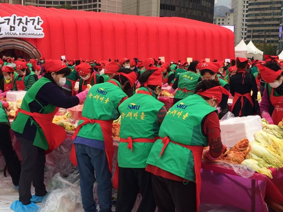 Koreanische Frauen und Männer bereiten Kimchi unter freien Himmel zu